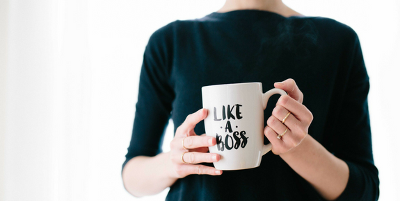 Woman holding a mug with like a boss slogan